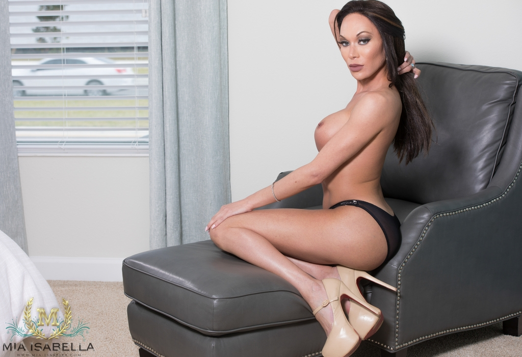 Mia isabella sits on a leather sofa and plays with her huge